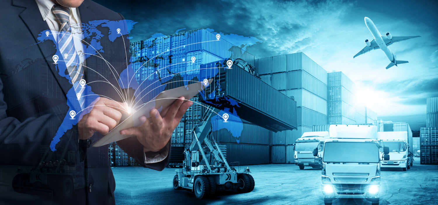 man on iPad in foreground of shipping dock with containers, freight carrying trucks and an airplane